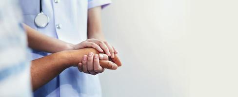 Krankenschwester und Patient Händchen haltend