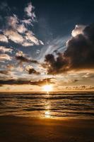 Sonnenuntergangshimmel über wehendem Meer foto