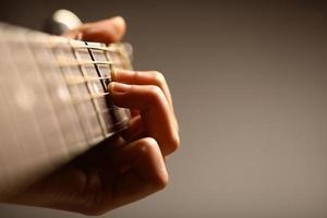 Nahaufnahme einer sechssaitigen Akustikgitarre, die gehalten wird foto