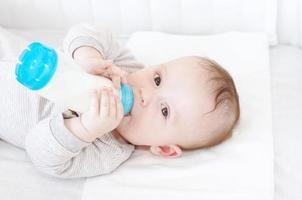 Baby mit kleiner Flasche im Bett foto
