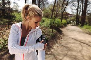 Läuferin überwacht ihren Fortschritt auf dem Smartphone foto