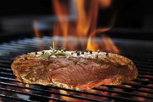 Gegrilltes Rindersteak auf dem brennenden Grill foto