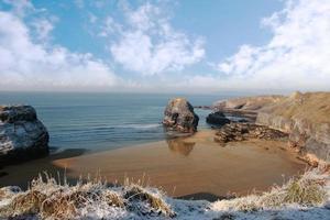 frostiger schneebedeckter Küstenstrand und jungfräulicher Felsen
