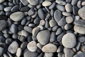 runde Kieselsteine auf dem schwarzen Strand, Texturhintergrund, Island