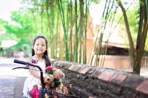 süßes kleines asiatisches Mädchen im Kleid, das eine rote Rose hält