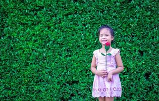 niedliches kleines Mädchen im Kleid, das eine rote Rose im Park hält