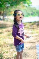 kleines Mädchen, das Zeltanker auf dem Campingplatz hält