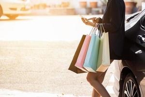 Person, die Smartphone verwendet, das Einkaufstaschen hält