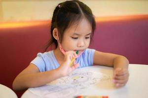 kleines Mädchen, das am Tisch sitzt und Bilder mit Bleistiften zeichnet