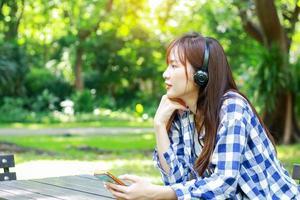 Frau, die Musik im Park hört foto