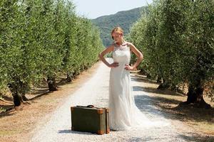 Braut mit Koffer auf Landstraße, Hände auf den Hüften