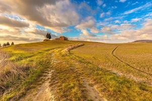 verlassene Gebäude zwischen den toskanischen Feldern mit blauen Wolken