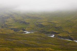 Island. Ostfjorde. Fluss und Berge mit Nebel.