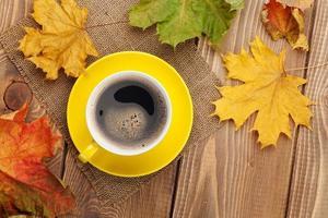 Herbstlaub und Kaffeetasse über Holzhintergrund