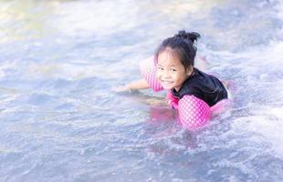 kleines asiatisches Mädchen im Wasser foto