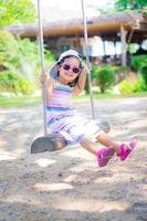 kleines Mädchen tragen Sonnenbrille auf einer Schaukel im Park
