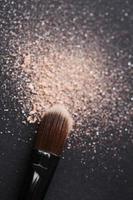 Puder auf schwarzem Hintergrund von Make-up Pinsel gestreut