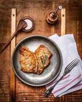 Gebratene marinierte Schweinesteaks auf rustikalem Küchentisch