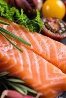 Portion frischer Lachs mit Gewürzen, Kräutern und Gemüse foto