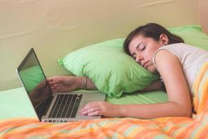 junge Frau, die beim Verwenden des Notizbuchs auf Bett einschlafen foto