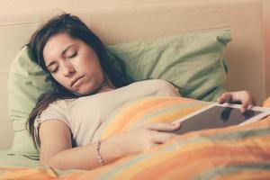 junge Frau, die beim Verwenden des digitalen Tabletts auf Bett einschlafen foto