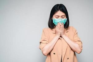 Frau, die eine Gesichtsmaske trägt, die niest und hustet foto