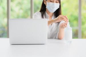 Frau, die eine Gesichtsmaske mit Desinfektionsmittel neben Computer trägt