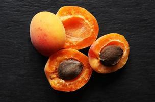 Aprikosen halbiert auf Schieferhintergrund