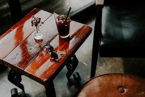 Getränk und Sonnenbrille auf quadratischem braunem Beistelltisch foto