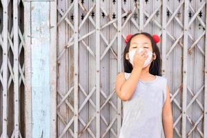 kleines asiatisches Mädchen, das eine gähnende Maske trägt