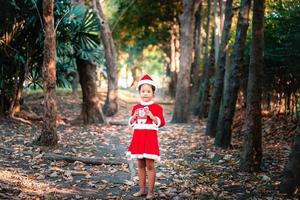 kleines asiatisches Mädchen im roten Weihnachtsmannkostüm foto