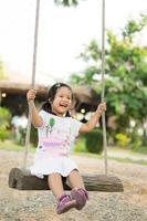 kleines Mädchen im weißen Kleid, das auf einer Schaukel im Park sitzt