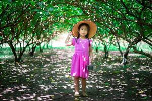 kleines asiatisches Mädchen, das die Maulbeerfrucht betrachtet