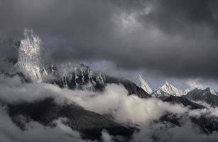 schneebedeckte Berggipfel unter dunklen Wolken in Nepal