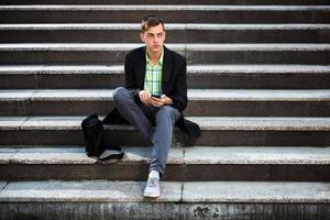 junger Mann mit einem Handy, das auf den Stufen sitzt foto