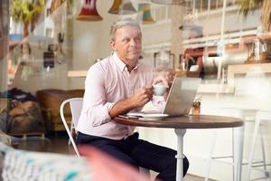 Mann mittleren Alters, der in einem Café sitzt foto