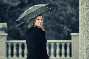 glückliche junge Modefrau mit Regenschirm im Regen