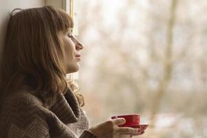 schönes Mädchen träumt mit Tasse Kaffee