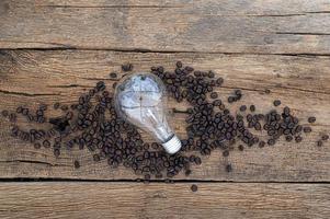 Glühbirne und Kaffeebohnen auf dem Schreibtisch