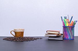Schreibwaren und Kaffee auf dem Schreibtisch