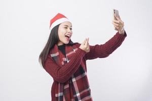 junge lächelnde Frau, die roten Weihnachtsmannhut trägt