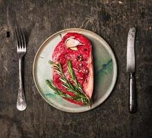 Streifenfiletsteak auf Teller mit Rosmarin, Knoblauch, Salz und Pfeffer