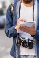fröhlicher bärtiger männlicher Tourist mit Pfanne und Notizbuch