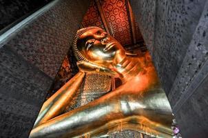 Gold liegendes Buddha-Statuengesicht. Wat Pho, Bangkok, Thailand foto