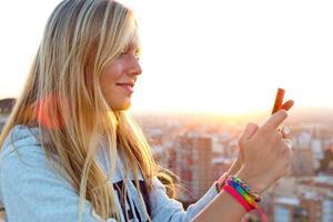 schönes blondes Mädchen, das Fotos von der Stadt macht.