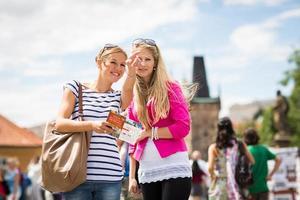 zwei weibliche Touristen, die entlang der Charlesbrücke gehen, Prag foto