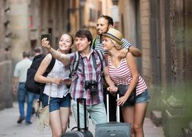 glückliche Reisende mit Gepäck machen Selfie