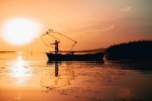Silhouette des Mannes, der Fischernetz in Gewässer wirft