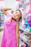 kleines Mädchen mit einer Puppe im Einkaufszentrum