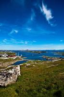 norwegische Sommerlandschaft mit Meer, grüner Wiese und tiefblauem Himmel